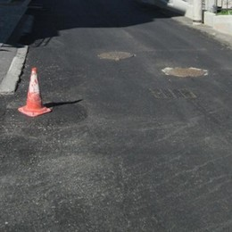 Grosio, dall'asfalto sconnesso  affiorano i tombini: via Martiri protesta